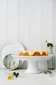 Mandelkuchen mit Zitronencreme auf einer weißen Kuchenplatte