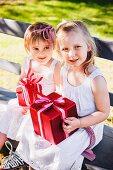 Zwei kleine Mädchen sitzen mit Geschenken auf Holzbank im Garten