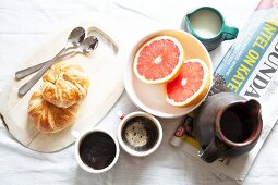 Breakfast with croissants, coffee, grapefruit and newspapers