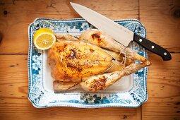 Roast chicken with lemon on a serving platter
