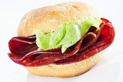 A bread roll filled with smoked beef and lettuce