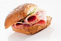 A wholemeal bread roll filled with ham, cucumber and radishes