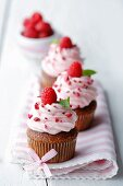 Raspberry cupcakes decorated with ribbon on a pink striped napkin with a bowl of raspberries in the background