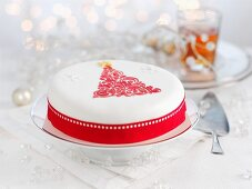 A white Christmas cake decorated with a red Christmas tree