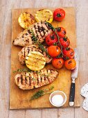 Grilled chicken breast, lemons, thyme and tomatoes on a wooden board