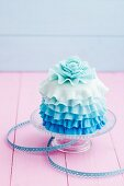 A mini cake decorated with blue icing
