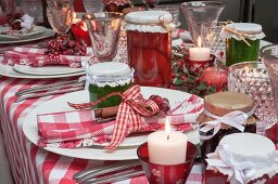 A Christmas table laid with a red checked tablecloth, napkins, jars of jam and candles