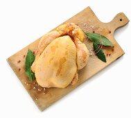 A raw corn-fed chicken on a chopping board