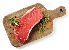 A raw rump steak on a chopping board