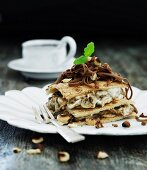 A layered dessert with nut cream, prunes and grated chocolate