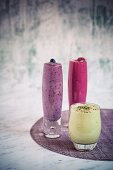 Various fruit smoothies (raspberry, blueberry and apple) in glasses
