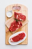 Various beef steaks and salt on a chopping board