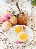 A jar of apple jelly and fresh bread rolls