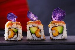 Three sushi rolls with salmon, avocado and purple potato crisps
