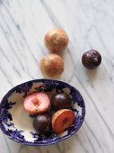 Plums and pluots (a cross between a plum and an apricot) in an antique dish and next to it