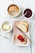 A mini loaf of white bread baked in a cup and served with butter and strawberry jam