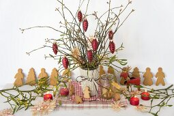 Christmas bouquet with red fir cones, glass decorations, straw stars, mistletoe and almond biscuits