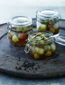 Pickled unripe strawberries in glass jars