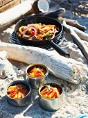 Penne pasta with chilli, and chicken with pepper for a Caribbean picnic on a beach