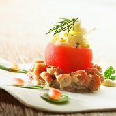 A tomato filled with chicory on a bed of prawn salad