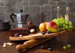 Chocolate cake and sweets on a chopping board being compared with fruit
