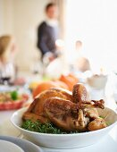 A stuffed turkey on a table laid for Thanksgiving