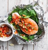 Raw salmon steak with tomatoes and baby spinach in aluminium foil (local)