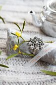 A linen napkin decorated with a sprig of mistletoe and a ring with a transparent strip of paper as a name tag