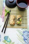 Sushi with soya beans on a bamboo mat with soy sauce (Japan)
