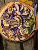 An autumnal pizza with pears, goat's cheese and red onions