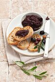 Tapenade with slices of bread and a sprig of olives