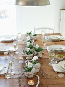 A wooden table laid with white pansies, tea lights and white wine
