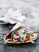 A spicy wrap with chicken, avocado, pepper and onions