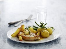 A pork chop with potatoes, green beans and apple wedges