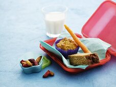 A lunchbox with a muffin, carrots, bread, dried fruits and milk