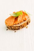 A slice of seeded bread topped with pepper and ricotta cream and basil