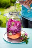 Water being poured over wild rose petals in a glass jar