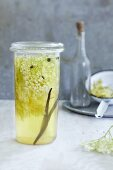 A jar of elderflower vinegar with a vanilla pod