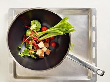 Tofu and raw vegetables in a wok