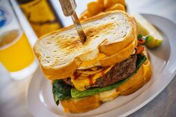 A burger between two toasted cheese sandwiches