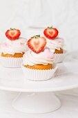 Three strawberry cupcakes on a cake stand