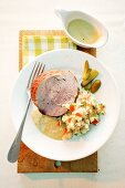 A sliced of turkey roulade with potato salad and gherkins