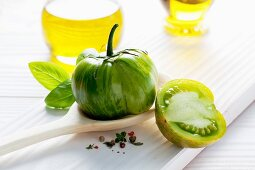 A green tomato on a wooden spoon