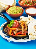 A pan of beef, onions and peppers with tortillas for fajitas