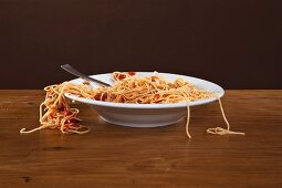 Spaghetti with tomato sauce with some stands hanging over the edge of the plate