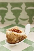 A Turkish walnut cake on a canapé spoon