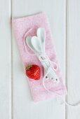 Erdbeere und Dessertlöffel auf rosa Tuch