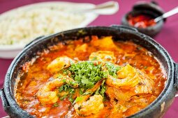 Moqueca (Brazilian stew with fish and prawns) in a terracotta pot with rice in the background