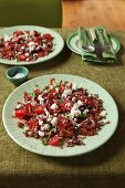 A red salad with rice, tomatoes, berries, herbs and spices