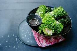 Savoy cabbage rolls filled with fish and sesame seeds (Asia)